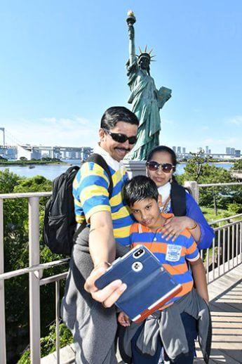 「お台場の女神像」を背景に写真を撮る観光客