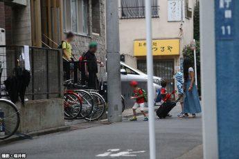 マンションを後にする欧米系男女(撮影・桜井修)